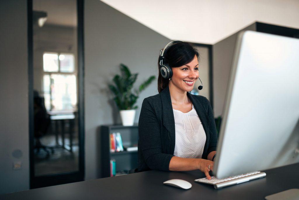 Frau am Computer mit Headset